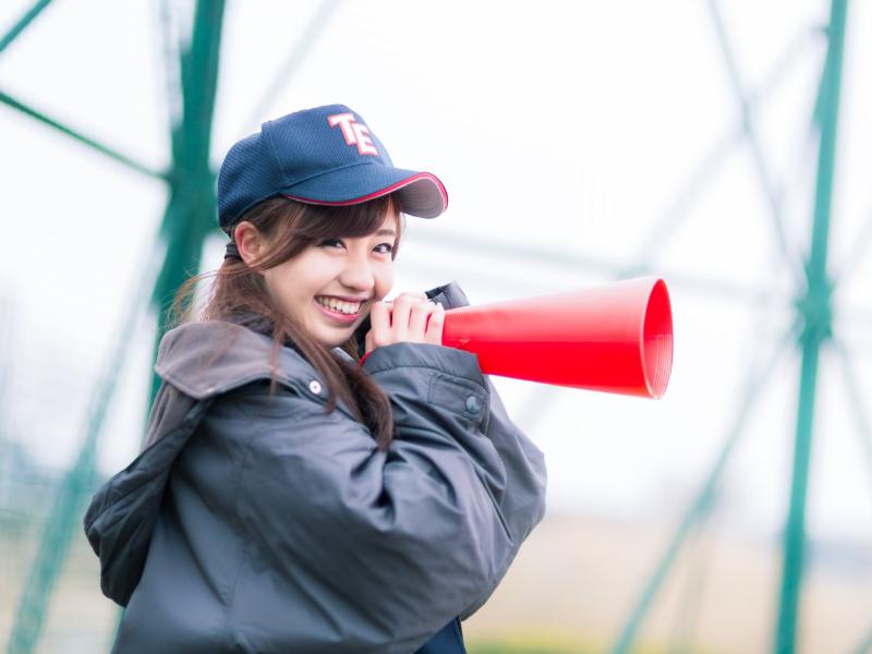 野球の応援をしている女子高生の写真